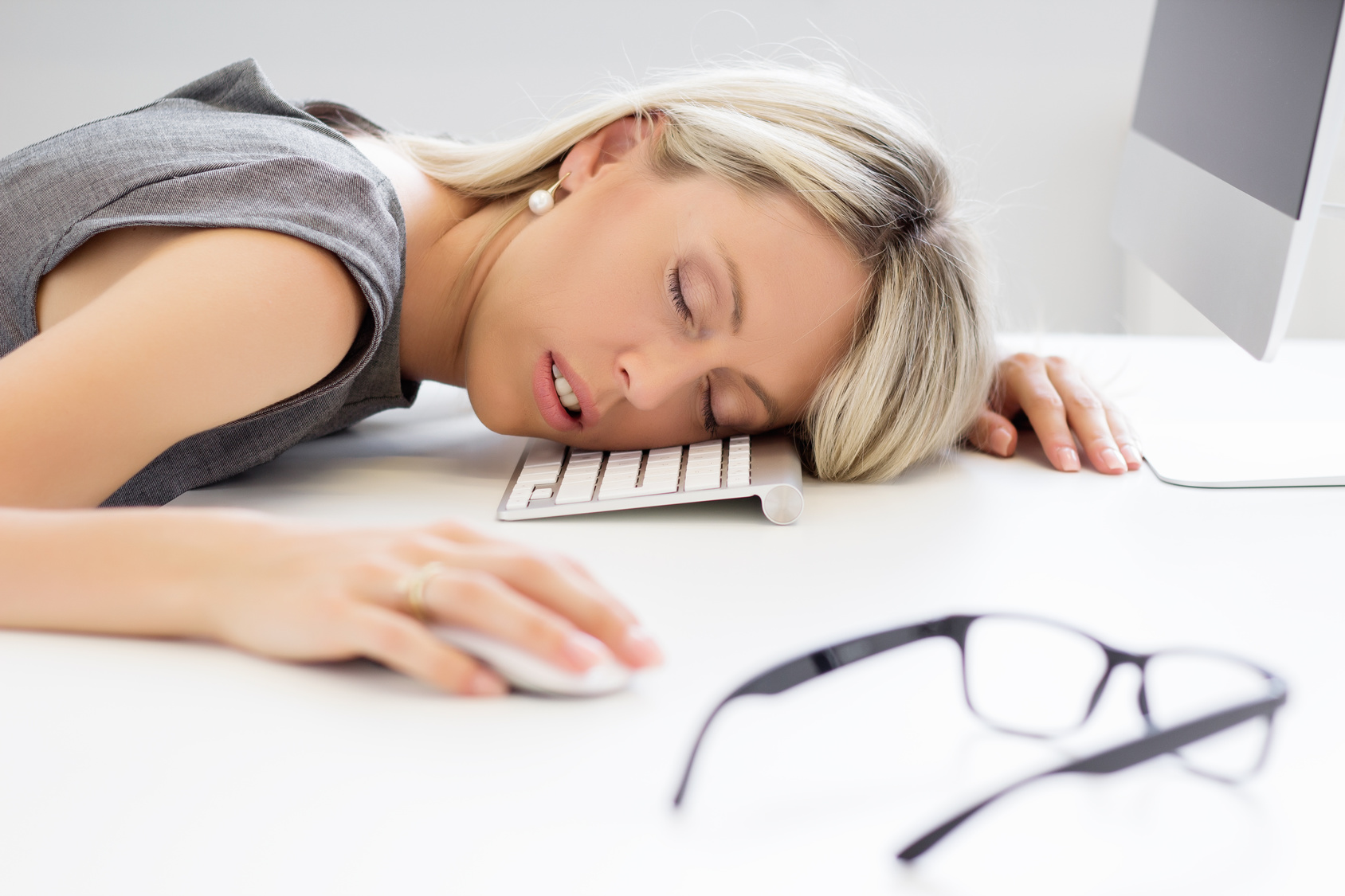 Exhausted woman sleeping in front of computer