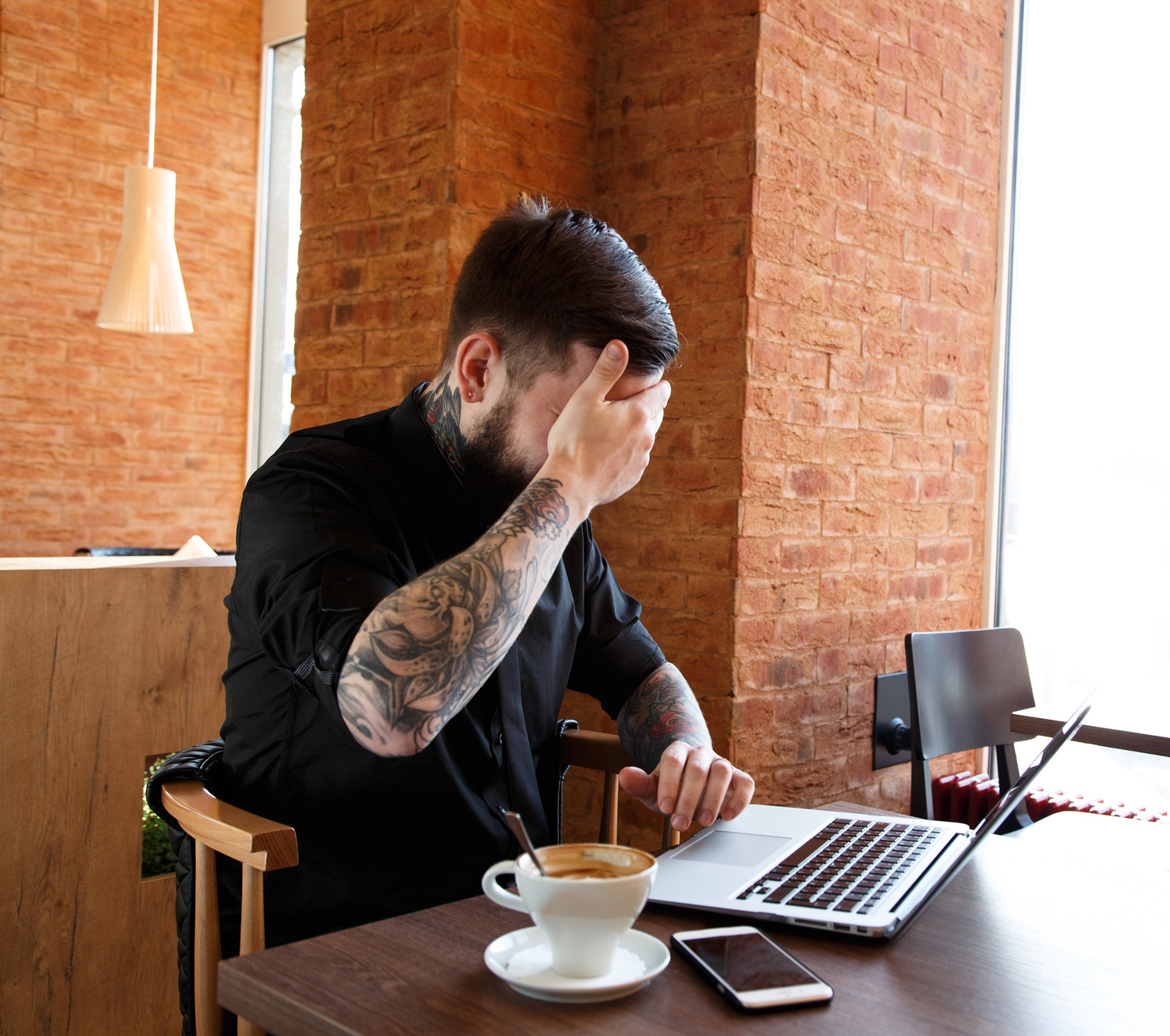 Man with tattoo facepalming