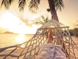 Female legs in a hammock on a sunset-lit beach
