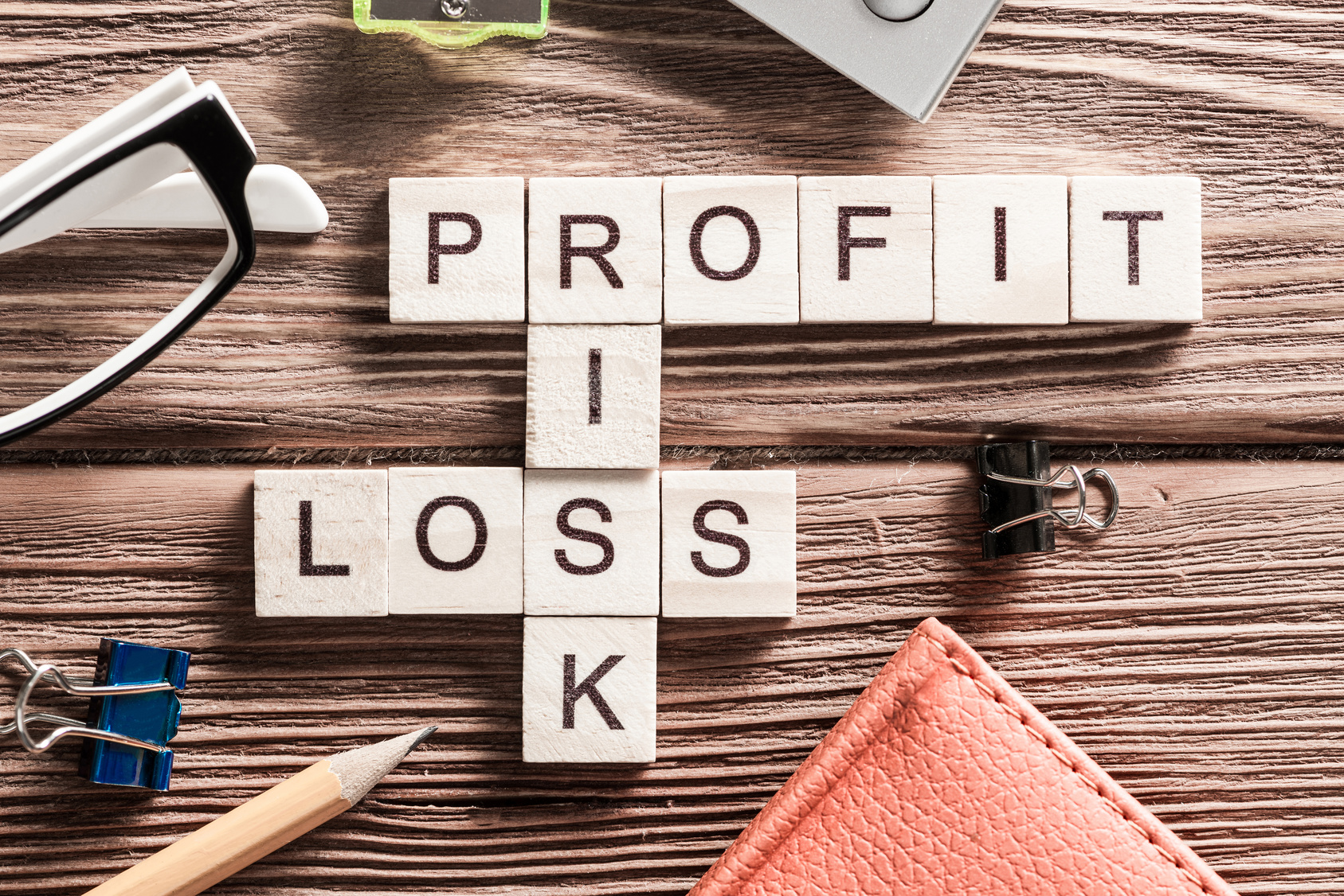 Profit, loss, and risk in letter tiles on cluttered desk