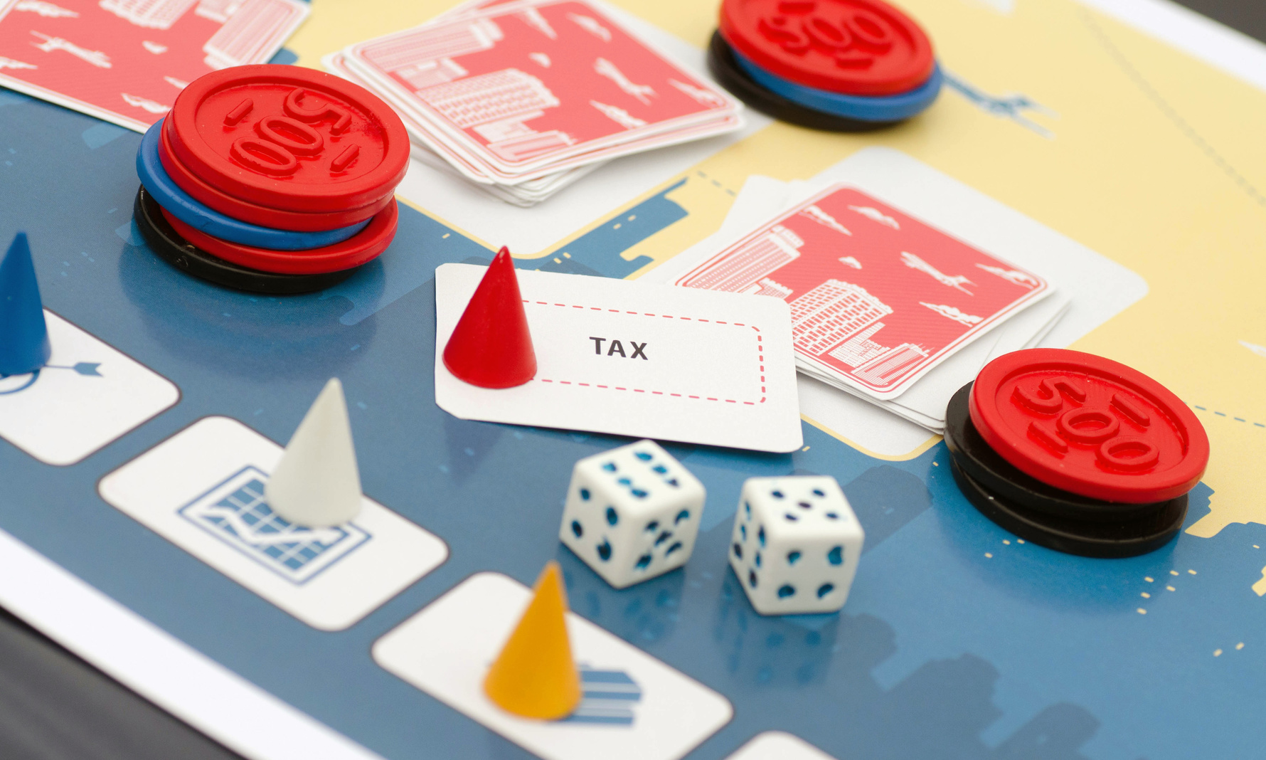 Board game prototype with cones, chips, dice, and card that says tax