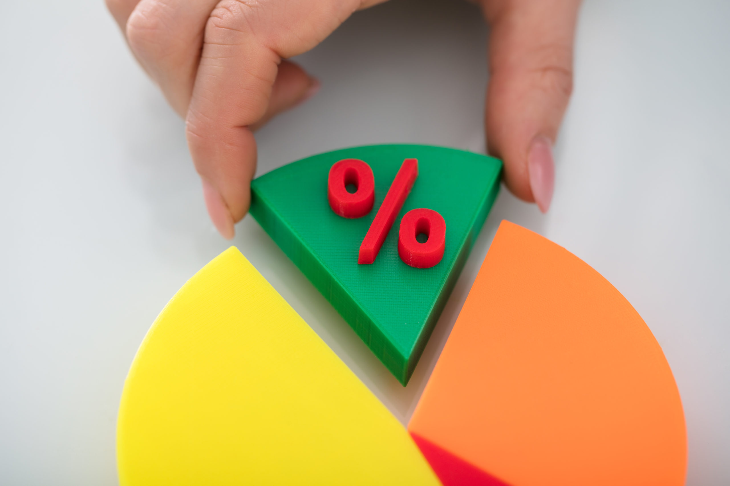 Close-up Of A Person's Finger Taking Green Piece Of Pie Chart With Red Percentage Symbol