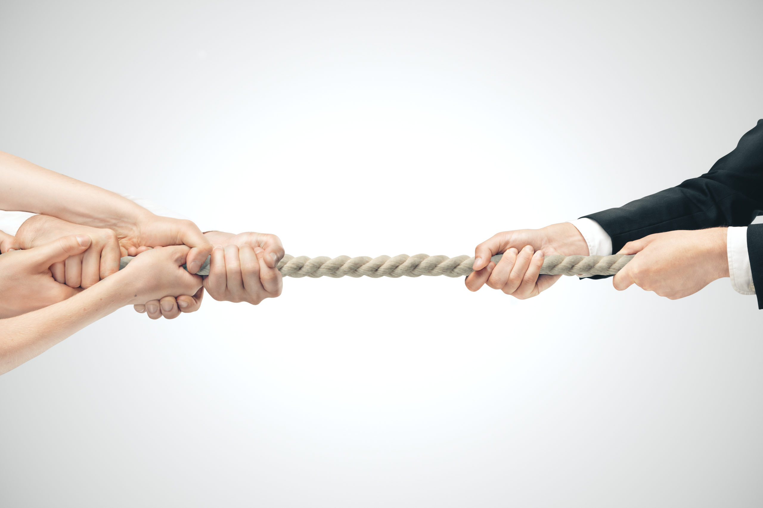 Hands playing tug of war with strong rope on white background